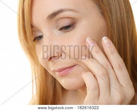 Senior woman applying anti-aging cream on face, closeup