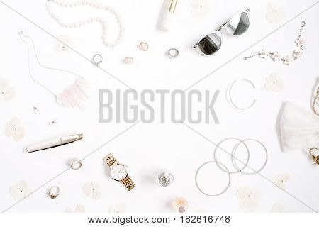 Beauty blog frame concept. Woman clothes and accessories: watches sunglasses bracelet necklace rings lipstick on white background. Flat lay top view trendy fashion feminine background.