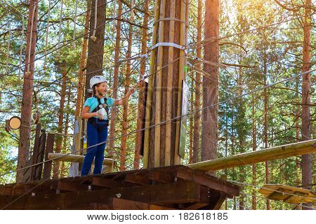 Teenage girl goes on hinged trail in extreme rope Park in summer forest. High-altitude climbing training of child on adventure track equipped with safety straps and protective helmet. Estonian summer
