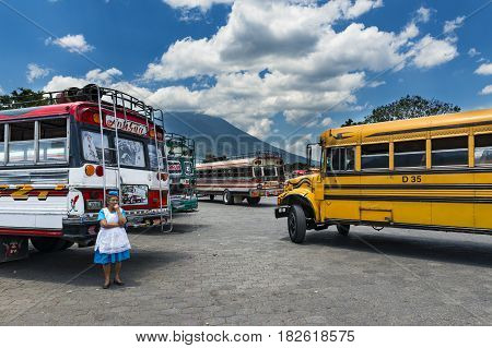 Antigua Guatemala - April 19 2014: Woman in a bus terminal with colorful buses in Antigua Guatemala