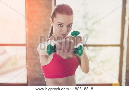 Close Up Portrait Of Young Sportwoman Concentrated On Her Work Out. She Looks Straight, Being Seriou