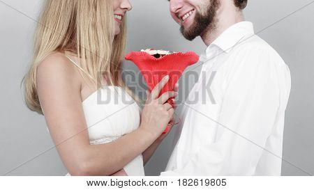 Closeup of loving couple with candy bunch bouquet flowers. Man and woman holding present gift. Relationship love concept.