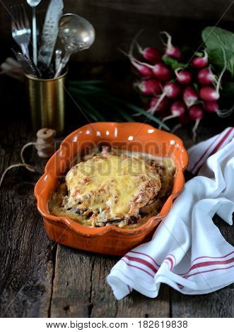 Chicken breast stuffed with mushrooms baked with potatoes under cheese.