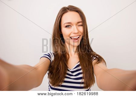 Young Cheerful Girl In Striped T-shirt Taking Selfie And Winking At Camera Against White Background