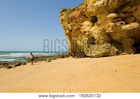 ALBUFEIRA, PORTUGAL - AUGUST 24, 2016: Person at the famous beach of Olhos de Agua in Albufeira. This beach is a part of famous tourist region of Algarve.
