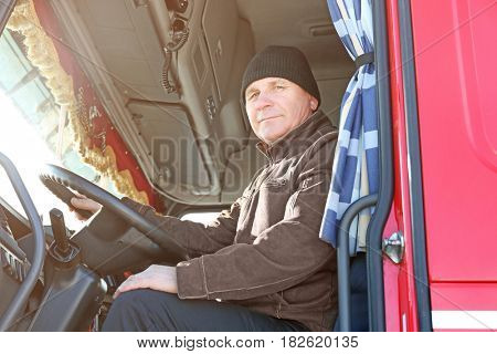 Elderly driver sitting in cabin of big modern truck