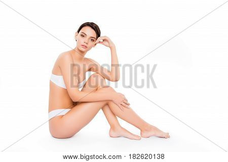 Young cute girl touching smooth legs and smilling
