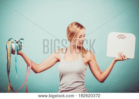 Diet healthy eating and slim body concept. Fit fitness girl holding bowl with many colorful measuring tapes as dieting symbol and weight scales studio shot on blue