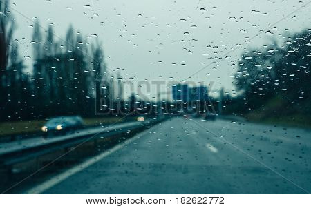 Water drops on wwindshield - Personal perspective of driver inside car looking at the front view of the highway autobahn on a heavy rain