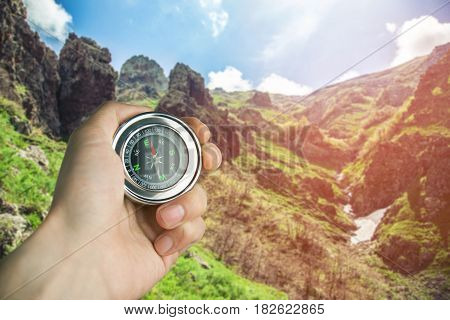 compass in hand man in rock background