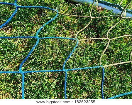 Detail of yellow blue crossed soccer nets soccer football in goal net with grass on outdoor playground in the background.