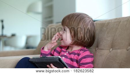 Cute little girl  sitting on coutch and using touchpad or tablet and smiling
