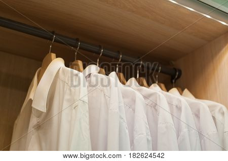 White men shirts hanging on the Trembler in closet