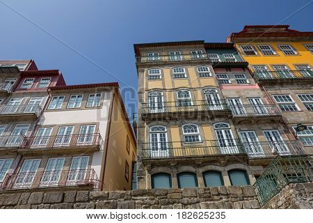 Porto, Portugal. April 17, 2017: The typical colorful buildings of the Ribeira District with shops, restaurants and bars built in the stone wall. Unesco World Heritage Site.