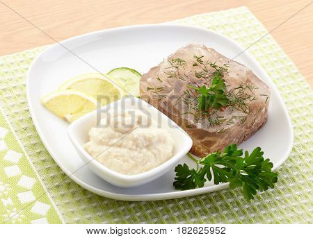 Aspic of beef on white plate with lemon, cucumber, horseradish and parsley