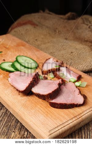 Close-up of sliced beef steak with cucumber on a cutting board on a wooden background slices of fat