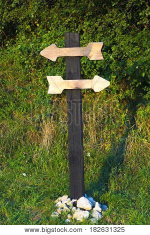 Wooden pole with two wooden planks in form of arrows for inscriptions. Wooden directional sign with two empty arrows