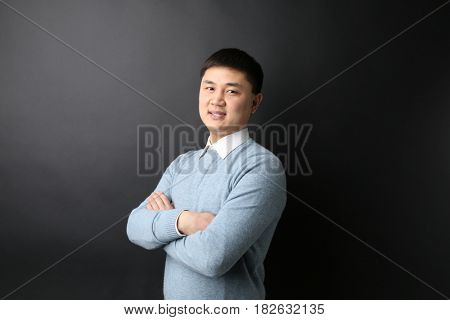 Handsome young Asian teacher on blackboard background