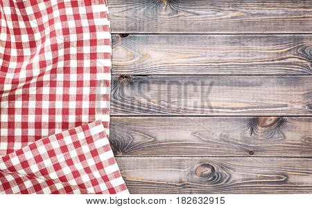 Red checkered tablecloth on light wooden table with, top view with copy space.