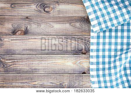 White old wooden table with blue checkered tablecloth, top view with copy space.