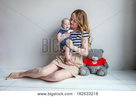 Young mother holding her newborn child. Mom nursing baby. Woman and new born boy relax in a white bedroom. Mother breast feeding baby. Family at home