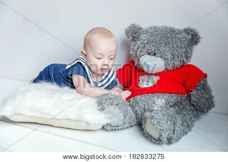 Infant child baby boy In a sailor's suit lies on his stomach on a pillow next to the teddy bear against a white wall background.