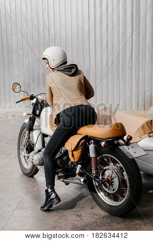 Smiling girl on a motorcycle. The photo of the girl from behind. Young woman on a motorcycle. Motorcycle kaferacers. White motorcycle with a large sidecar. Wow