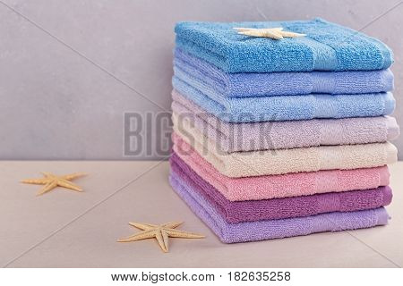 Stack of colorful bath towels with sea stars on light background. Pastel colors cotton or bamboo towels. Hygiene fabricspa and textile concept