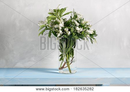 Spring snowflake Leucojum vernum bouquet in glass vase on blue wood table and gray background