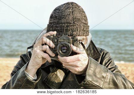 Photographer with retro photo camera on sea beach look at camera.Retro style toned image.