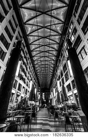 BERLIN - OCTOBER 08 2016: Heiligegeistkirchplatz - narrow street and covered shopping area in the center of Berlin. Black and white.