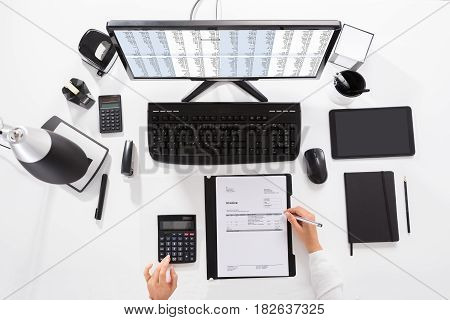 Elevated View Of A Businesswoman Calculating Invoice On Desk At Workplace