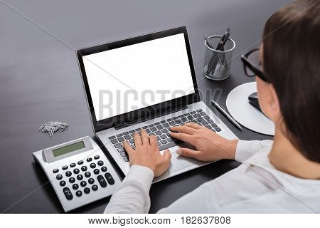 Rear View Of A Woman Typing On Laptop At Workplace