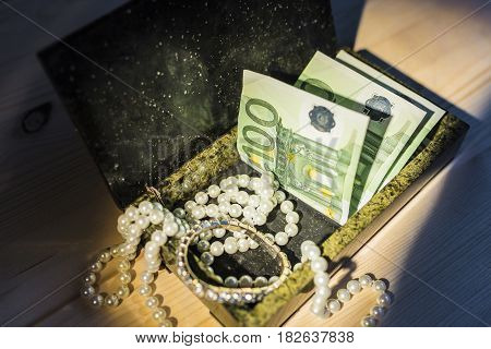 Denominations of one hundred euros, a bright pearl necklace, a brilliant bracelet with diamonds in a green malachite box under the rays of light on a wooden background. Financial stability concept.