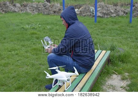 A Man With A Remote Control Quadroopter In His Hands Is Sitting On A Bench. White Quadroopter Prepar