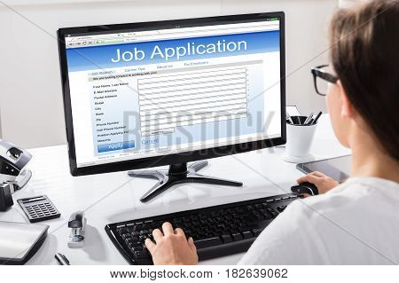 Rear View Of A Woman Filling Job Application On Desk