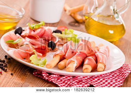 Grissini breadsticks with ham and olives on white dish.