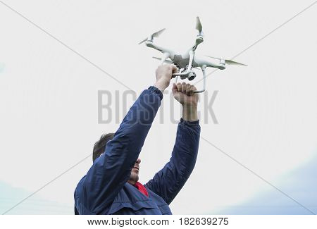 A Man With A Quadrocopter In His Arms Raised To The Sky. A White Drone Is Being Prepared For The Fli