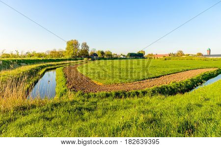 Agrarian landscape with grass plowed field and ditches in a Dutch polder area. It is in the beginning of the spring season.