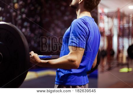 Strong crossfit athlete man in a heavy overhead squat lift in a box gym
