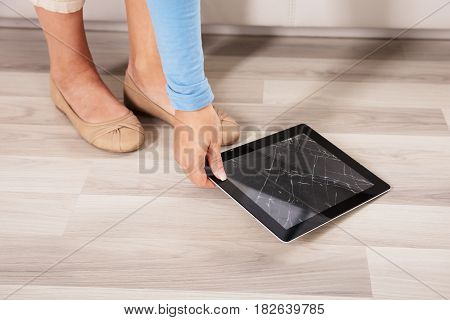 Close-up Of A Woman Picking Up The Broken Digital Tablet From Hardwood Floor