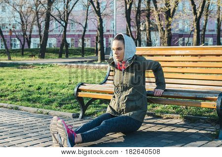 Young Woman In A Jacket And A Hood Doing Exercises On Triceps On A Bench In The Park In Spring