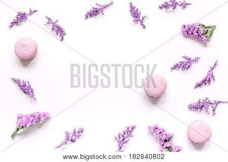 lady morning with macaroons and mauve flowers on white desk background top view mock-up