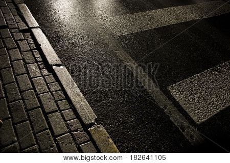 Road at midnight illuminated with car lamps