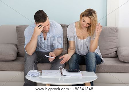 Worried Young Couple Sitting On Couch Calculating Bills At Home