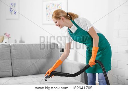 Woman cleaning couch with vacuum cleaner