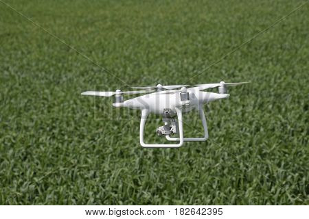 Russia, Poltavskaya village - May 1, 2016: Flying white quadrocopters over a field of wheat. Flying gadget for video.