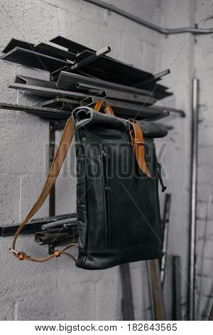 Exclusive black leather backpack. Backpack near the wall. The tools in the garage. Many different tools on the wall .Metal pipes near the wall