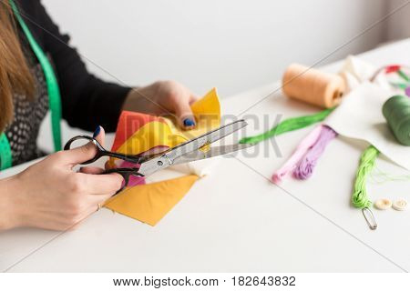 needlework and quilting in workshop of a young woman tailor - tailor cuts with scissors a piece of quilted fabric on table in the background of lying tools and spools of thread, fabric and pins
