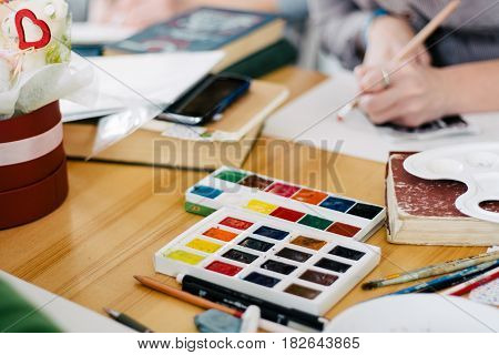 Pretty smiling young woman drawing a picture with poster paint. Front view on drawing girl with palette in her hand. Smiling young woman draw a picture at studio